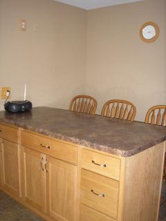 Large countertop at breakfast bar with high back swivel stools.  Ceiling light projects down on bar.