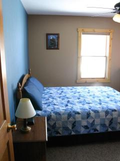 The blue bedroom has a queen size bed, ceiling fan, night stand, dresser, and clock radio.