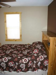 A full size bed in the brown bedroom offers a built-in headboard / shelf and reading light.