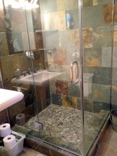Pebble floor in shower in private bath with heated floors