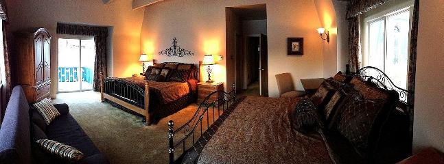 Master Suite: 2 king beds, sleeper sofa, desk, flatscreen TV, and a private deck.