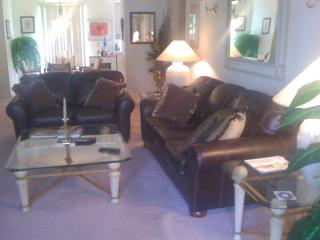 Large living room features new couch, love seat and chair with ottoman.
