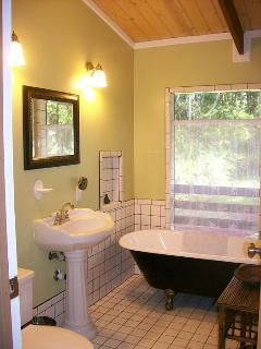 Art nouveau inspired bathroom with pedestal sink and claw foot tub