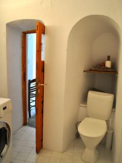 Inside bathroom, toilet alcove on right washing machine just visible on left side.