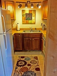 Fully equipped left unit kitchen with fridge, microwave, stove, dishwasher and more.