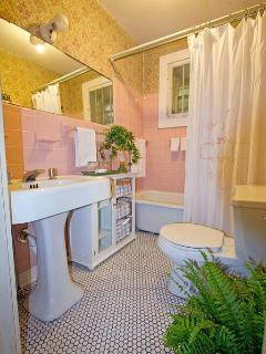 Vintage bathroom, original soaking tub with shower option, original sink, black & white tile