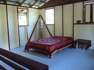 The upstairs bedroom with a private porch overlooking the garden and the river