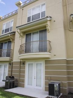 Rear of townhome showing walk-out patio and second floor balcony