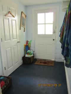 Entrance to Downstairs hallway with beach towels and beach accessories, next to bathroom with laundr