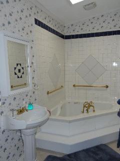 Pool Cabin's bathroom - large whirlpool bath with shower.