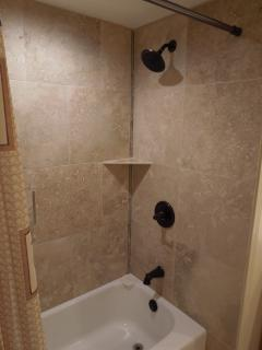 elegant travertine tiled shower with oil rubbed bronze fixtures