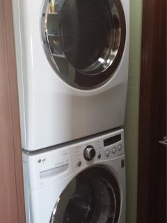 Stacked full size LG washer and dryer in laundry.