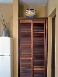 A small closet with louver doors to hang your beach clothes.