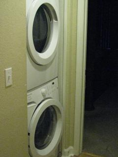 Front load washer and dryer in hallway between the bedrooms