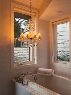 Candle lit glittering antique crystal chandelier above Zen bath tub overlooking deck
