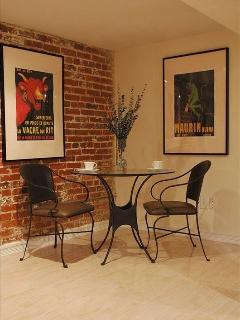 Bistro style dining nook with exposed brick and Parisian posters.