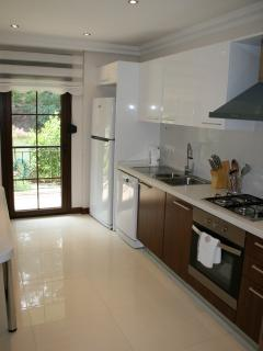 Kitchen with all white goods and dinner service