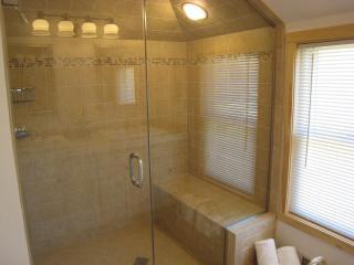 Master bathroom with glass-enclosed shower, radiant-heated floors, and double vanity sinks.