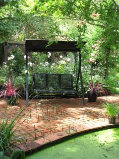 Swing seat in the shade next to the garden pond