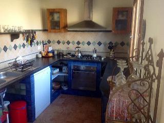 kitchen with tiled floor,decorative backsplash, lava rock counter