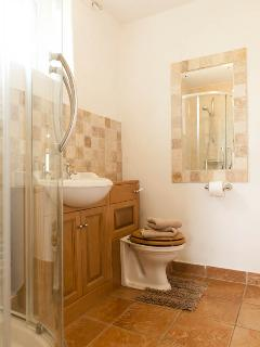 The ground floor shower room with spacious shower cubicle, basin & toilet is under floor heated.