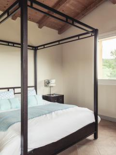 Master bedroom with king sized bed and ensuite bathroom.