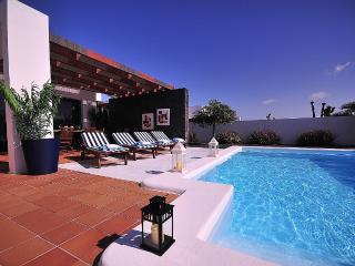 Terrace with heated pool and sun loungers.