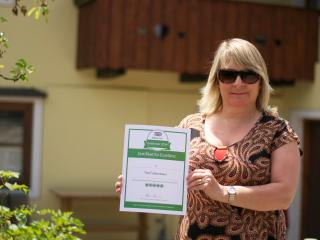Dawn the owner with the Certificate of Excellence Award from Trip Advisor for The Farberhaus!