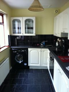 Fully functioning kitchen with washing machine, cooker, microwave, and fridge freezer.
