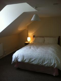 Double bed in spacious room.