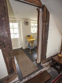 Dining area to the right with highchair visible