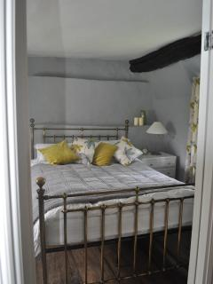 King size bed in a soft grey and lime green colour scheme, original ceilings and elm floor boards.