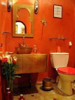 Salle de bain de la chambre Carmin avec douche, lavabo toilettes, coffre fort et sèche cheveux