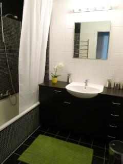 Bathroom with bath tub / shower combination, towels,  shampoo, hairdryer and iron.