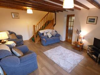Living room with a welcoming three piece suite, TV & DVD player.