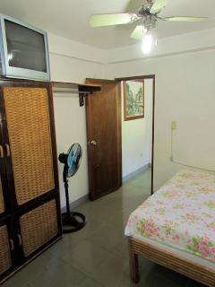 Master bedroom with queen sizebed, tv, desk, air conditioning, electric fan, large armoire, desk