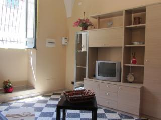 Salottino con divano-letto, parete attrezzata con tv