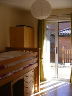 Bedroom 3, with patio doors to decking area and patio.