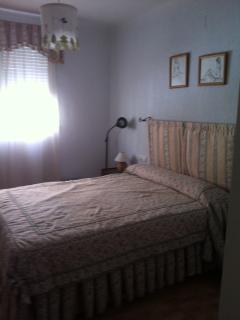Dormitorio principal con gran armario y cama de matrimonio.