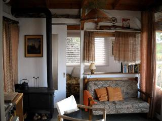 Living area with single bed behind double sleeper sofa and woodstove