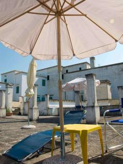 Terrazza a 1°piano con ombrelloni, sedie-regista e lettini ad uso degli ospiti,lato ovest