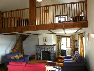 The Lounge, showing 3 sofas, log burning stove and gallery above.