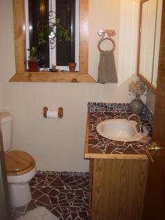 Downstairs bathroom contains custom tile mosaic with local beach rock and shower