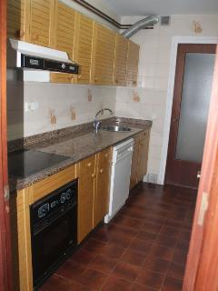 Cocina equipada con lavavajillas, lavadora, microondas, horno y nevera.