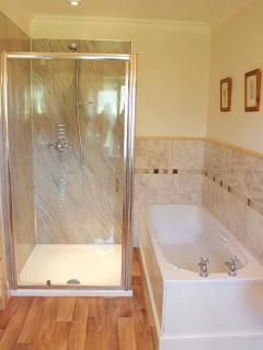 En-suite bathroom with walk in Aqualisa shower, loo, wash-hand basin and bath.