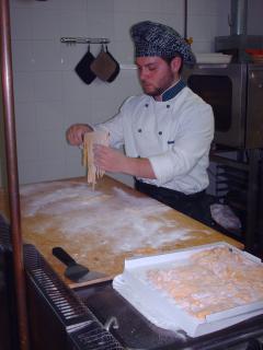Lo chef sta facendo le tagliatelle all'uovo.