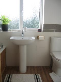 Upstairs part tiles bathroom with modern suite and airing cupboard