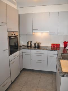 modern fully equipped kitchen with granite work tops, oven, microwave, toaster and kettle