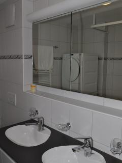 Double sinks, the bathroom also houses a washing machine and dryer