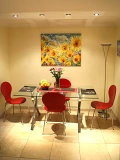Bright dining area with limestone floor and underfloor heating. Modern dining table and chairs.